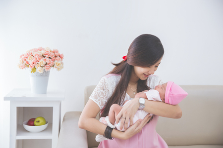 Asian woman holding her sleeping baby girl Stock Photo