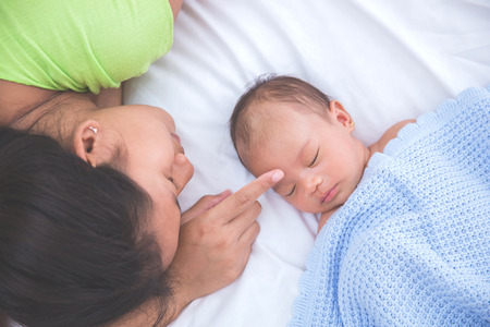 asian baby: Asian baby sleeping with woman touching her forehead, admiring