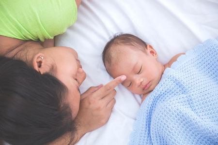ni�o durmiendo: Beb� asi�tico que duerme con la mujer tocando su frente, admirando Foto de archivo