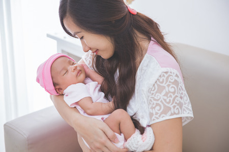 Asian woman holding her sleeping baby girl, close up Archivio Fotografico