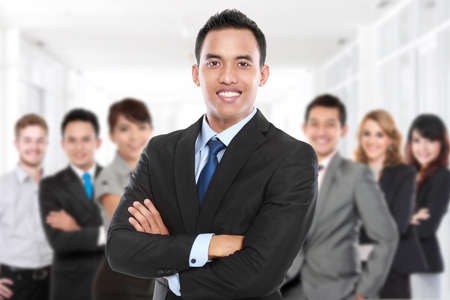 squad: Businessman with his team member behind. smiling with crossed arms Stock Photo