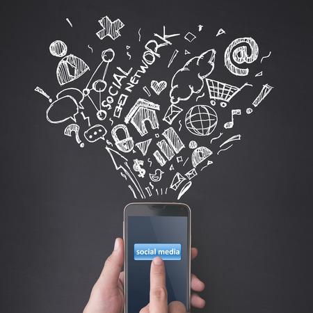 medios de comunicacion: Dedo presionando el botón de medios de comunicación social en el teléfono inteligente en el fondo pizarra