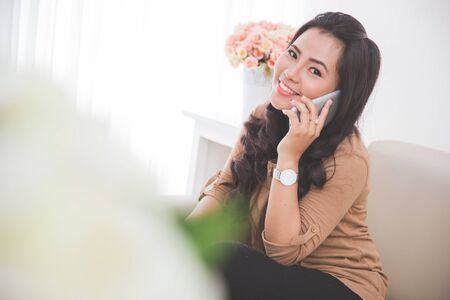 woman on couch: portrait of  asian Woman sitting on a couch, calling friend with smartphone Stock Photo