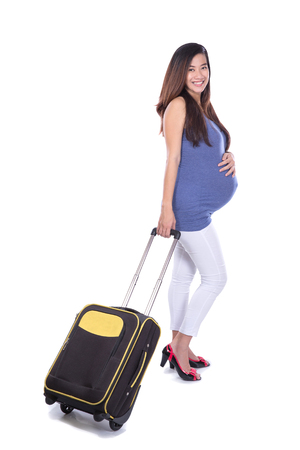A portrait of an Asian pregnant woman bring a suitcase in white background. ready for traveling