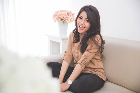 cheerfully: Woman sitting on a couch looking cheerfully