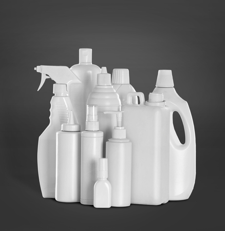 toxic: detergent bottles and chemical cleaning supplies over grey background