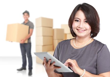parcel: Woman holding tablet pc smiling to camera with a courierman and boxes in the background