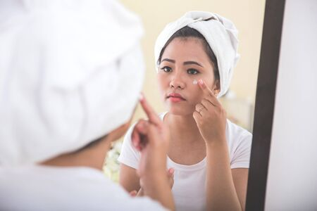 applying: Woman applying skincare lotion into her face, smiling at the mirror