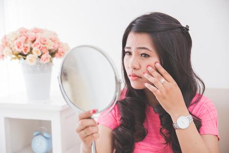 Vrouw met een spiegel, touch en zorgen te maken over haar gezicht