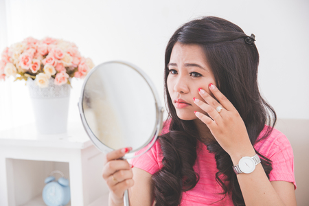 Woman holding a mirror, touch and worrying about her face Imagens