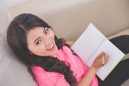asian lady: Woman holding notebook sitting on a couch, writing, looking up