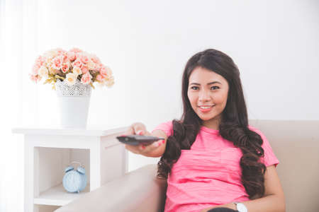 changing channel: Woman sitting on a couch, using remote control to changing channel on television Stock Photo