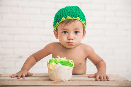 baby face: A portrait of a Cute caucasian boy wearing a green knit hat with a bread in front of him