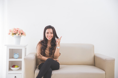 Woman sitting on a couch, pointing to blank white wall up. ready for your design Stock Photo