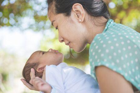 madre y bebe: Retrato de una mujer sosteniendo su oudoor niña