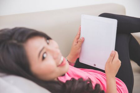 woman laying: Woman laying on a couch using a tablet pc, taken from behind and her head turned Stock Photo