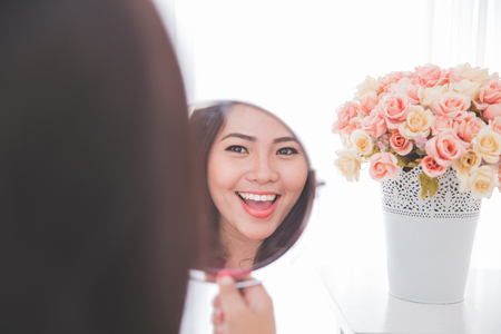 Woman holding a mirror, smiling brightly looking at her face Foto de archivo