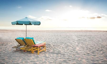 sillon: Un retrato de un par de sillas de playa con el paraguas en una orilla del mar