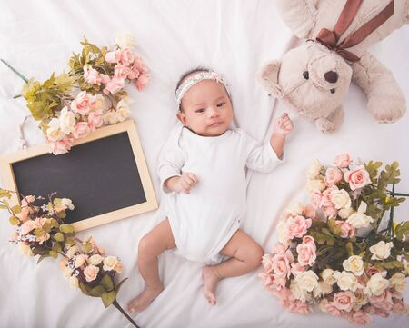 baby doll: A portrait of a Cute asian baby girl on white blanket with flowers, bear doll and blank chalkboard Stock Photo