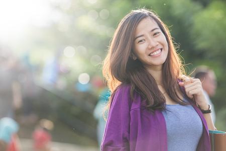 Un retrato de una hermosa mujer asiática sonriendo alegremente a la cámara