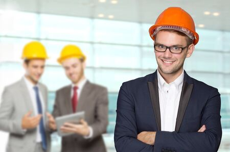 A portrait of a young businessman wear a safety helmet. team working at the back Imagens
