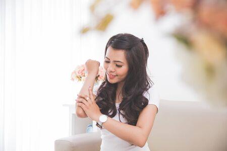 mujer maquillandose: Mujer que aplica mosturizing loción en su piel, concepto de tratamiento Foto de archivo