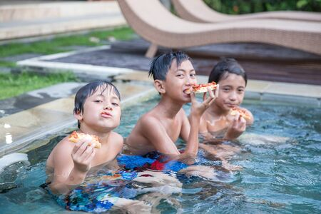 A portrait of three boys enjoying the pool while eating pizza Stock Photo