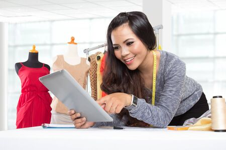 rested: A portrait of a young asian designer woman using a tablet pc, smiling rested on a table, clothes background