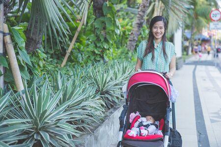 ni�o empujando: retrato de la mujer a dar un paseo con su beb� en el cochecito de beb� Foto de archivo