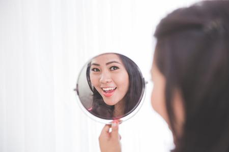 espejo: Mujer que sostiene un espejo, sonriendo alegremente mirando a la cara