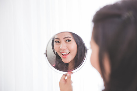 reflection: Woman holding a mirror, smiling brightly looking at her face Stock Photo