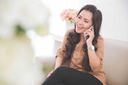 PRETTY WOMEN: portrait of  asian Woman sitting on a couch, calling friend with smartphone Stock Photo