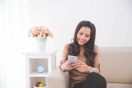 woman on couch: Woman sitting on a couch, using a smartphone. Smiling away Stock Photo
