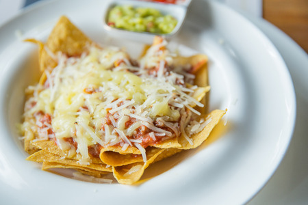 A close up potrait of mexican food nachos with sauce and cheese