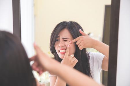 女性は鏡を彼女の頬ににきびを絞る