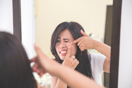 Woman squeezing pimples in her cheek, look at the mirror