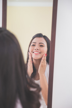 looking in mirror: Woman applying skincare lotion into her face, smiling at the mirror