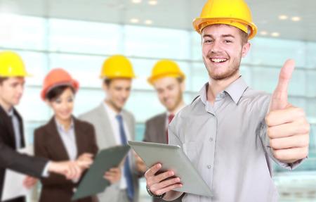 Portrét mladého podnikatele nosit ochrannou přilbu ukazuje palcem