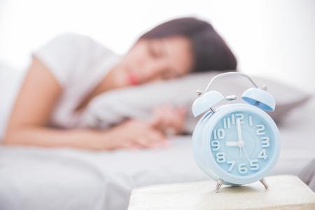 Alarm clock close up with woman sleeping peacefully on a bed on the back