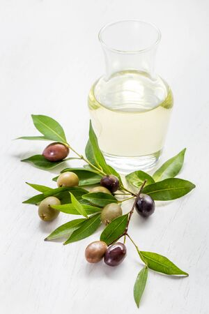 poured: portrait of olive oil with green olives and black olives isolated on white