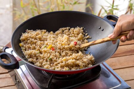 spicy cooking: portrait of people cooking homemade spicy fried rice Stock Photo