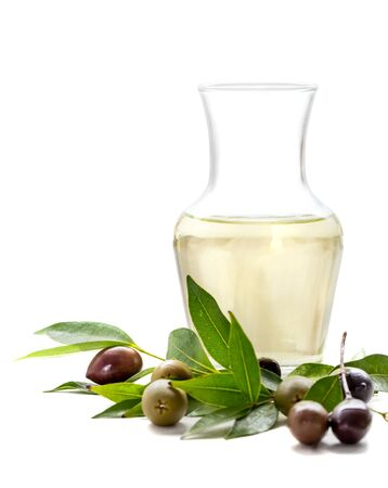 poured: a bottle of olive oil with green olives and black olives isolated on white background