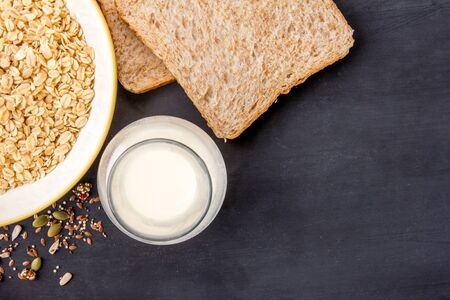 delicious food: a bottle of milk, dry bread, and oatmeal for breakfast with copy space on black board for background