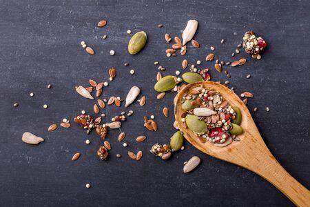 avena: retrato de los granos de cereales saludables en la cuchara de madera con tablero negro para el fondo