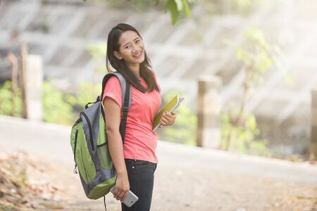 jovenes estudiantes: Un retrato de un joven estudiantes asiáticos en su actividad al aire libre, de pie y la inclinación de la cabeza de ella a la cámara Foto de archivo