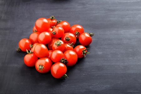 tomate cherry: montón de tomates cherry con copia espacio a bordo de negro para el fondo