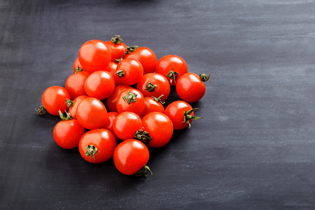 cherry: pile of fresh cherry tomatoes with copy space on black board for background