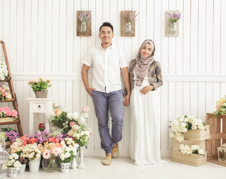 full view portrait of happily married couple standing and smiling at decorated room