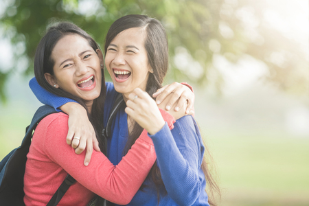 laughs: A portrait of happy two young Asian students laugh, joking around together Stock Photo
