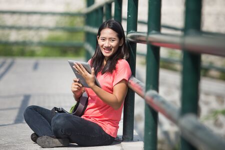 A portrait of a young Asian student in her outdoor activity, holding a tablet pc while sitting.